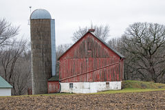 Silo Next to a Weathered Red Barn with a White Foundation Stock Photography