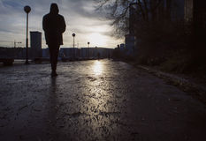 Silohouette del hombre que camina en una calle húmeda al día melancólico en últimos otoño/invierno, Imagen de archivo libre de regalías