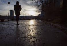 Silohouette do homem que anda em uma rua úmida um o dia sombrio no outono/inverno atrasados, Imagem de Stock Royalty Free