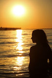 Silohoutte of Woman and sunset. Silhouette of woman by waters edge at sunset Royalty Free Stock Photography