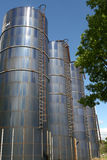 Silos. Four blue farm silos against blue sky stock image
