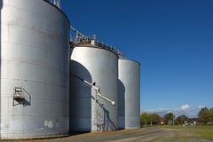 Silos on Blue Sky 1. Large silos on a clear day, with drop pipe showing Stock Image
