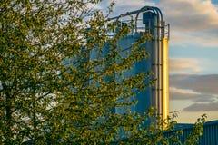Silos de la fábrica en la puesta del sol Foto de archivo libre de regalías