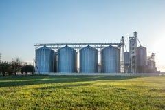 Silos de prata na planta deprocessamento para o processamento e o armazenamento dos produtos agrícolas, da farinha, dos cereais e imagens de stock