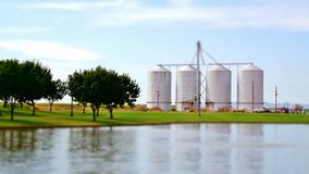 Silos durch Bauernhof und See Lizenzfreies Stockbild