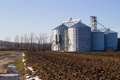 Silos for grain on a plowed field Royalty Free Stock Images