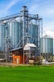 Silos industriales debajo del cielo azul, en el campo Foto de archivo libre de regalías