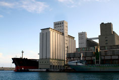 Silos in port with cargo freights Royalty Free Stock Photos