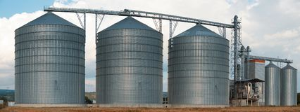 Silos. Storage and drying of grains, wheat, corn, soy, sunflower against the blue sky. Panorama. Panorama agricultural Silos. Building Exterior. Storage and Stock Photography