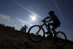Silouette of child on bike Stock Photo