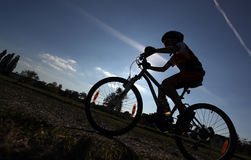 Silouette of child on bike Stock Images