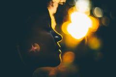 Silouette de la muchacha rizada joven durante puesta del sol Foto de archivo