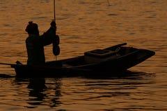Silouette de pêcheur dans le bateau de pêche sur l'eau Photos stock