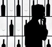 Silouette di un cameriere contro la bottiglia ed i vetri Fotografia Stock