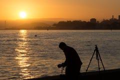 Silouette di un fotografo che prende una foto Fotografia Stock