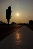 Silouette girl. Walk on the road with sunset Royalty Free Stock Images