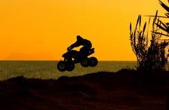 Silouette van vierlingfiets het springen Stock Foto's