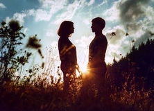 Silouettes de lever de soleil des deux jeunes d'inlove Photos libres de droits