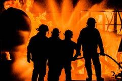 Silouhette av brandmän som rymmer linjen Arkivfoton