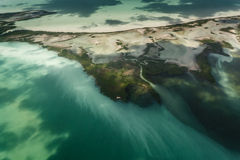 Silt and run off from island pollute barrier reef. Silt and run off from island streak the ocean with pollution and threaten the fragile coral barrier reef Stock Images