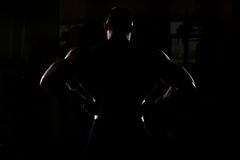 Siluet Bodybuilder Man Posing In The Gym. Silhouette Bodybuilder Posing - Handsome Power Athletic Guy Male - Fitness Muscular Body Stock Photos