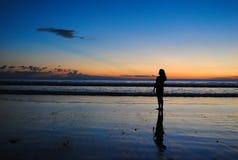 Siluet de una muchacha con la reflexión en tiempo de oro Imagenes de archivo