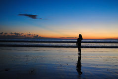 Siluet di una ragazza con la riflessione nel tempo dorato Immagini Stock