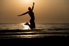Siluet Female With Raised Hands And Jumping Around. Silhouette of Woman With Raised Hands And Jumping Around on the Beach at Sunset - Copy Space Text Royalty Free Stock Photography