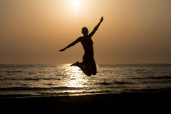 Siluet Girl With Raised Hands And Jumping Around. Silhouette of Woman With Raised Hands And Jumping Around on the Beach at Sunset - Copy Space Text Royalty Free Stock Photos