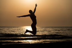 Siluet Girl With Raised Hands And Jumping Around. Silhouette of Woman With Raised Hands And Jumping Around on the Beach at Sunset - Copy Space Text Royalty Free Stock Photography