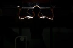 Siluet manlig bodybuildingidrottsman nen Doing Pull Ups royaltyfria foton
