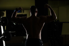 Siluet Mięśniowy mężczyzna Napina mięśnie W Gym Obrazy Stock