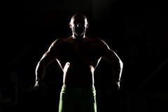 Siluet Muscular Man Flexing Muscles Stock Images