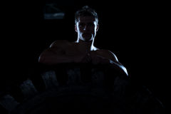 Siluet Portrait Of Muscular Man With Tire. Siluet Portrait Of Muscular Young Man With Tire Royalty Free Stock Photography