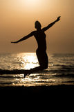 Siluet Woman With Raised Hands And Jumping Around. Silhouette of Woman With Raised Hands And Jumping Around on the Beach at Sunset - Copy Space Text Stock Images
