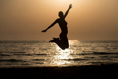 Siluet Woman With Raised Hands And Jumping Around. Silhouette of Woman With Raised Hands And Jumping Around on the Beach at Sunset - Copy Space Text Stock Photos