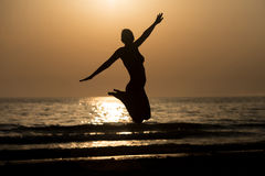 Siluet Woman With Raised Hands And Jumping Around. Silhouette of Woman With Raised Hands And Jumping Around on the Beach at Sunset - Copy Space Text Stock Photo