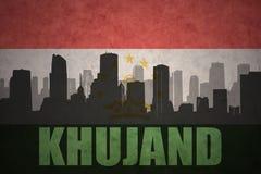Silueta abstracta de la ciudad con el texto Khujand en la bandera de Tayikistán del vintage fotografía de archivo libre de regalías