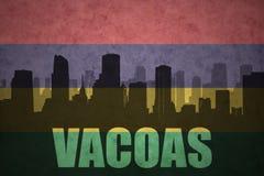 Silueta abstracta de la ciudad con el texto Vacoas en la bandera de Mauricio del vintage foto de archivo libre de regalías