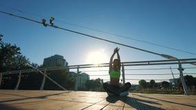 Silueta activa de la mujer que ejercita y que estira yoga en ciudad en pasarela almacen de metraje de vídeo