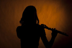 Silueta adolescente de la muchacha del jugador de flauta en amarillo Imagenes de archivo