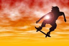 Silueta adolescente del muchacho con el patín que salta en la puesta del sol Foto de archivo