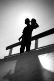 Silueta adolescente que anda en monopatín Fotografía de archivo libre de regalías
