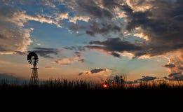 Silueta africana del molino de viento en la puesta del sol Imágenes de archivo libres de regalías