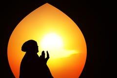 Silueta anaranjada hermosa de los musulmanes que ruegan en la mezquita Fotos de archivo