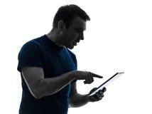 Silueta ansiosa de la tableta digital de la pantalla táctil del hombre Foto de archivo