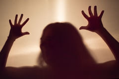 Silueta asustadiza femenina detrás de una pared de la tela Imagen de archivo libre de regalías