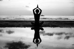 Silueta blanco y negro de la mujer de la yoga que medita en la orilla de mar Relájese fotografía de archivo