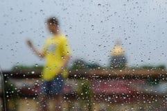 Silueta borrosa de un hombre en una camiseta amarilla con el teléfono detrás del vidrio mojado Foto de archivo libre de regalías