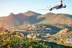 Silueta borrosa del aeroplano que vuela sobre las montañas foto de archivo